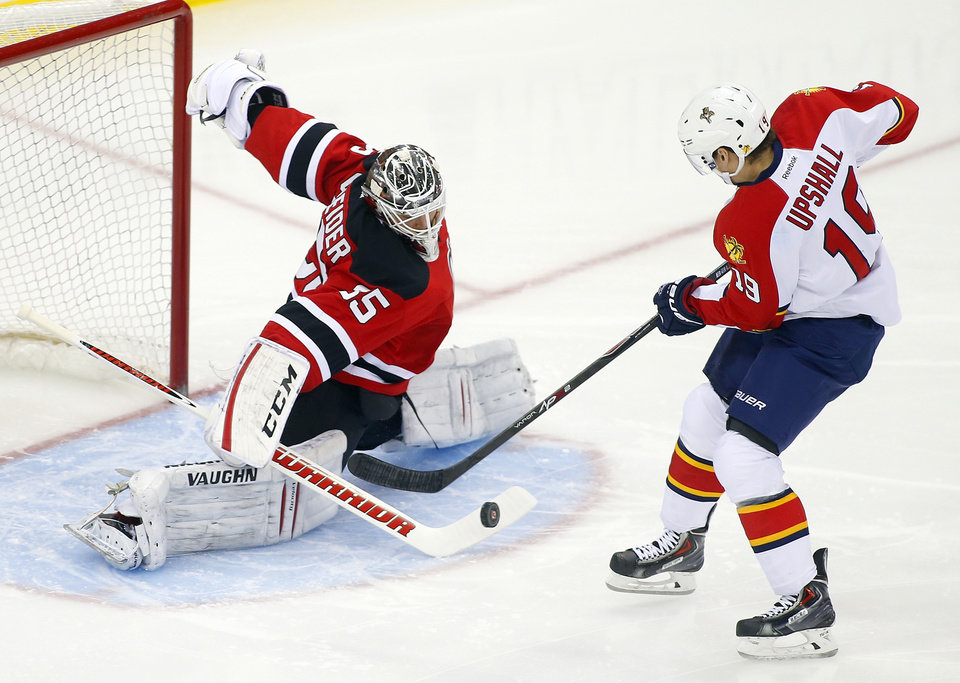 Photo - New Jersey Devils goalie Cory Schneider (35) makes a save on a shot by Florida Panthers' Scottie Upshall (19) during the first period of an NHL hockey game in Newark, N.J., Saturday, Jan. 11, 2014. (AP Photo/Rich Schultz)