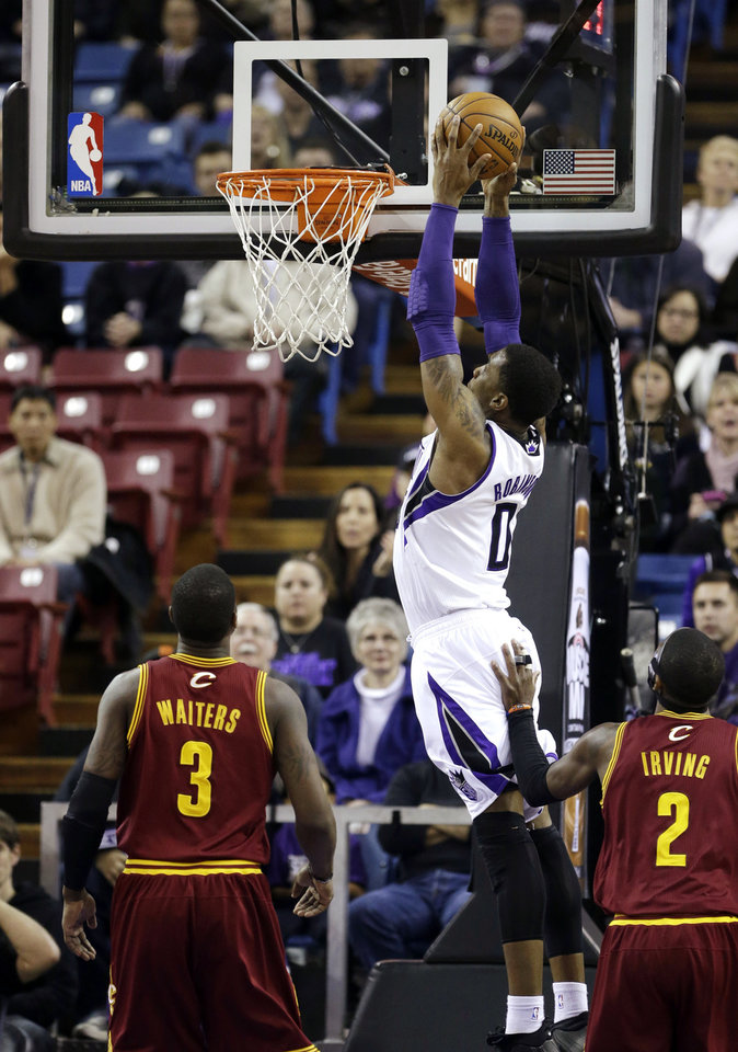 Sacramento Kings forward Thomas Robinson, center, dunks between Cleveland Cavaliers' Dion Waiters, left, and Kyrie Irving during the first quarter of an NBA basketball game in Sacramento, Calif., Monday, Jan. 14, 2013. (AP Photo/Rich Pedroncelli)