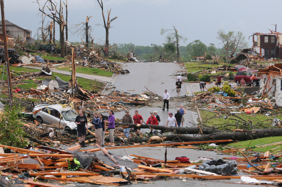 Residents of Joplin, Mo, survey the damage after a tornado hit the city on Sunday, May 22, 2011. The tornado tore a path a mile wide and four miles long destroying homes and businesses. (AP Photo/Mike Gullett) ORG XMIT: MOMG104