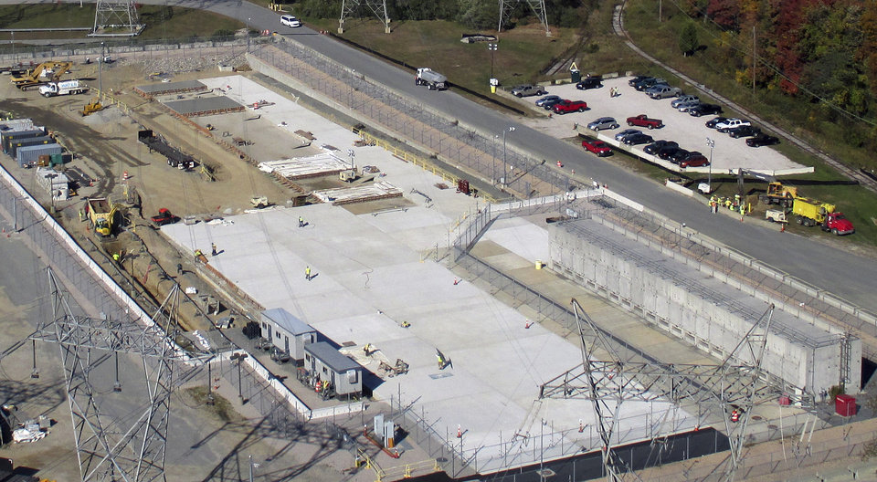 Photo - This Oct. 21, 2013 aerial photo released by Dominion Resources, shows an area where spent radioactive waste is stored at the Millstone Power Station in Waterford, Conn. Nineteen existing horizontal storage modules are on the right, and a new concrete pad to house more units is under construction, center. That construction was subsequently completed. With the collapse of a proposal for nuclear waste storage at Nevada's Yucca Mountain, Millstone and other plants across the country are building or expanding on-site storage for waste.(AP Photo/Dominion Resources)