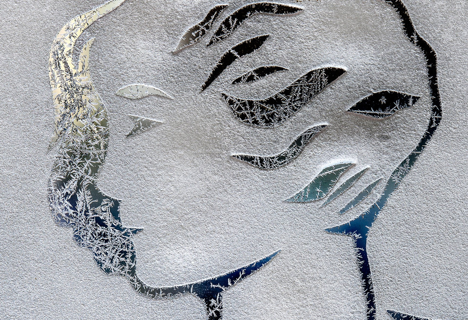 Photo - Ice crystals form on the outside glass of a dancing figure etched into the front glass doors of the Madison Theatre in Peoria, Ill., as temperatures dropped to near sub-zero with a new blast of winter chill, Tuesday, Jan. 21, 2014. (AP Photo/Journal Star, Fred Zwicky)