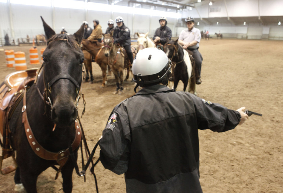 Deputy Sam Shesnut fires a handgun loaded with blanks during an annual training event to qualify deputies and horses for the Oklahoma County Sheriff's Office Mounted Patrol Division at State Fair Park in Oklahoma City, OK, Saturday, March 5, 2011. By Paul Hellstern, The Oklahoman ORG XMIT: KOD