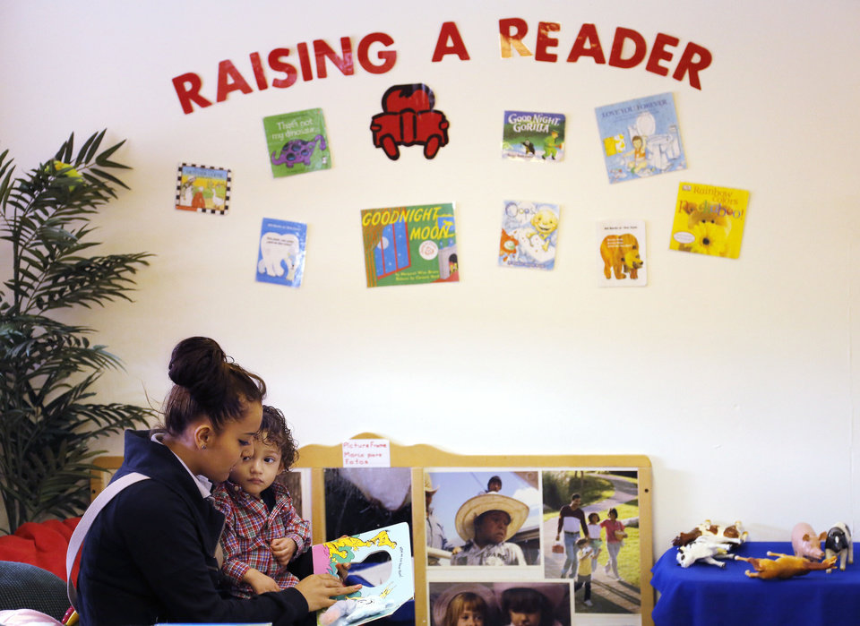 Photo - Karla Rodriguez reads to her son, Izack Perez, 1, Friday at Emerson High School.    Photo by Doug Hoke, The Oklahoman