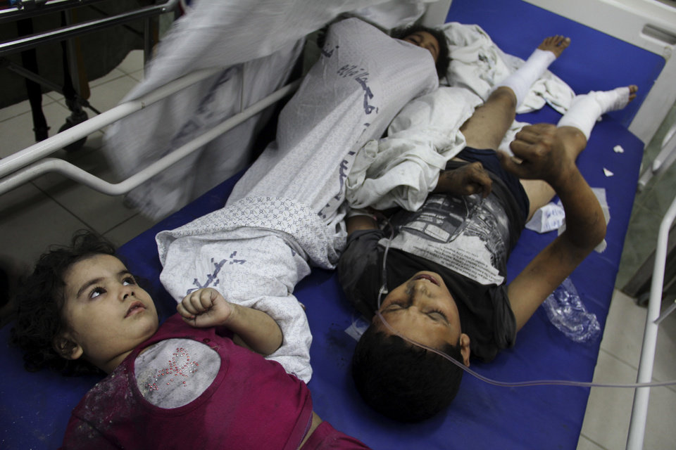 Photo - Palestinians children wait for treatment, following an Israeli airstrike on a building, at the treatment room of al Najar hospital in Rafah in the southern Gaza Strip, Thursday, Aug. 21, 2014. (AP Photo/Hatem Ali)