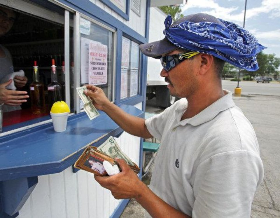 Photo - Paving company employee Omar Ibarra buys a sno cone from Eskimo Sno on Lindsey Street in 100 degree heat on this week.  STEVE SISNEY - THE OKLAHOMAN