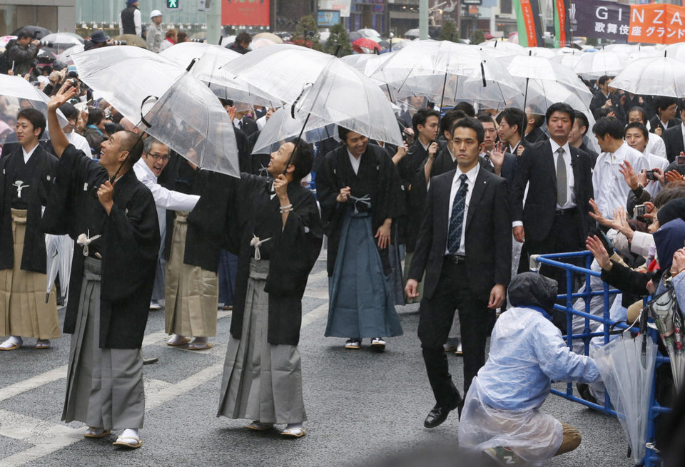 Photo - Kabuki actor Ebizo Ichikawa, left, Ennosuke Ichikawa, center, and other actors parade at Ginza shopping district in Tokyo, Wednesday, March 27, 2013. Some 60  actors paraded in the rain Wednesday to newly renovated Tokyo theatre ahead of its official opening. (AP Photo/Shizuo Kambayashi)