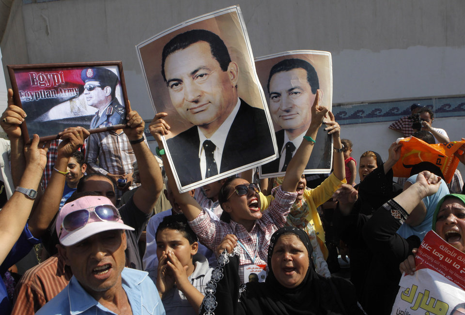 Photo - Supporters of former Egyptian President Hosni Mubarak hold his posters and a poster of Egyptian Army Chief Lt. Gen. Abdel-Fattah el-Sissi, left, in front of Tora prison where he has been held, in Cairo, Thursday, Aug. 22, 2013. Mubarak has been released from jail and taken to military hospital in Cairo. (AP Photo/Amr Nabil)