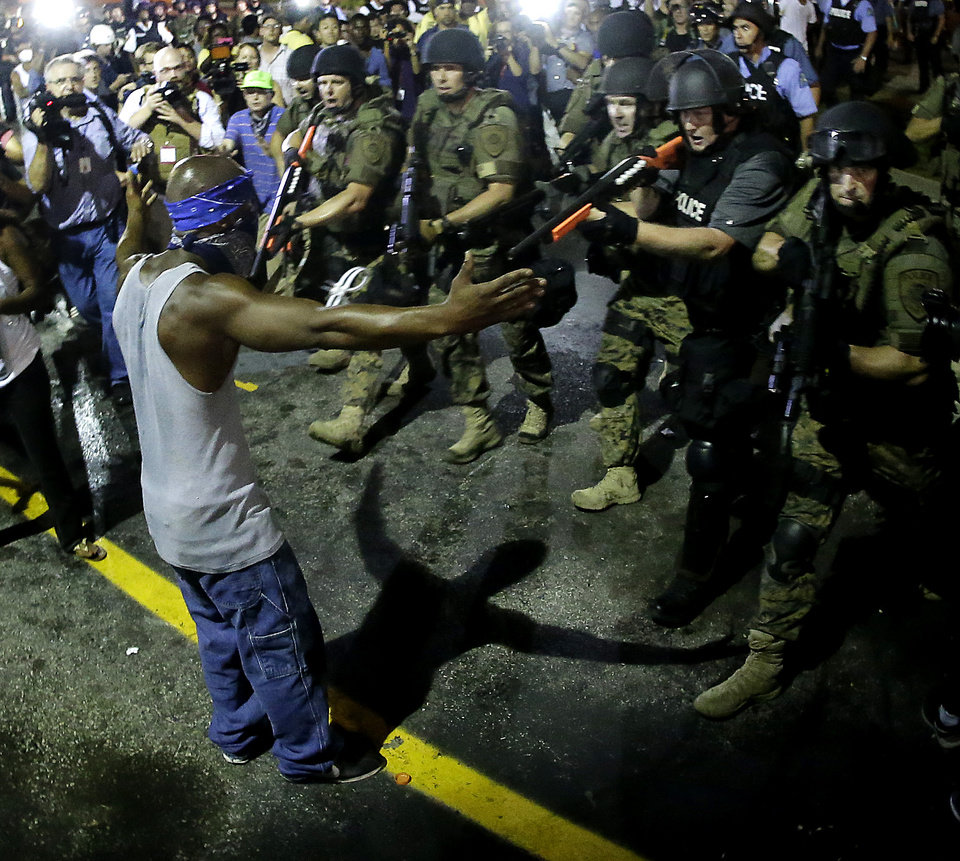Photo - Police arrest a man as they disperse a protest in Ferguson, Mo., early Wednesday, Aug. 20, 2014. On Saturday, Aug. 9, a white police officer fatally shot unarmed 18-year-old Michael Brown, who was black, in the St. Louis suburb. (AP Photo/Charlie Riedel)