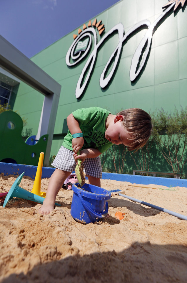 Photo - In this July 3, 2014 photograph, Brayden Squyres, 2, of Brandon, concentrates on filling his bucket with sand in the Desert Island Exploration sand pit at the Mississippi Children's Museum in Jackson, Miss. The interactive hands-on facility promotes literacy, health and nutrition, learning the state's heritage and exploration of its cultural arts and key economic industries in a fun setting. (AP Photo/Rogelio V. Solis)