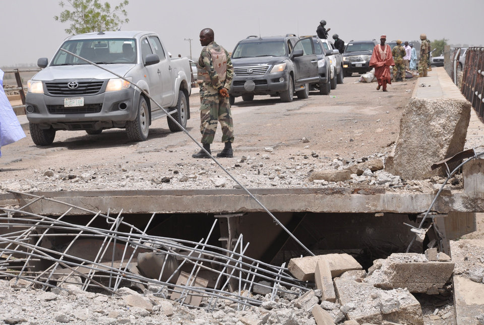 Photo - In this photo taken Sunday May 11, 2014. A soldier and other government officials inspect the bridge that was bombed following an attack by Islamic militants last week in Gambaru, Nigeria.  Many brutalized residents of the once bustling town of Gamboru say they are moving across the border to Cameroon because they cannot trust the Nigerian government to protect them, after repeated attacks by Islamic militants, including an attack a few days ago that killed some hundreds of people with more than 1,000 shops, dozens of homes and 314 trucks and cars bombed and burned out. (AP Photo/Jossy Ola)
