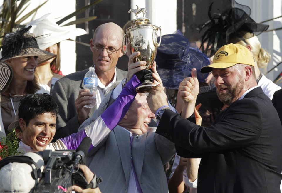 Jockey Mario Gutierrez ,  left,  owner J. Paul Reddam , middle, and trainer Doug O'Neill hold the trophy after I'll Have Another won  the 138th Kentucky Derby horse race at Churchill Downs Saturday, May 5, 2012, in Louisville, Ky. (AP Photo/Mark Humphrey) ORG XMIT: DBY214