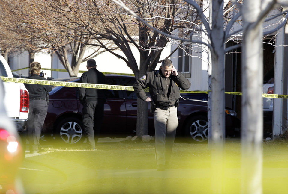"Photo - Police work behind a cordon of crime scene tape, at the scene of an apparent murder-suicide, which officials say left four dead inside a home, according to officials, in Longmont, Colo., Tuesday Dec. 18, 2012. Weld County sheriff's spokesman Tim Schwartz says dispatchers heard the woman who called 911 scream ""No, no, no,"" and then they heard a gunshot. Schwartz says a man grabbed the phone and said he was going to kill himself, and dispatchers heard another shot.  (AP Photo/Brennan Linsley)"