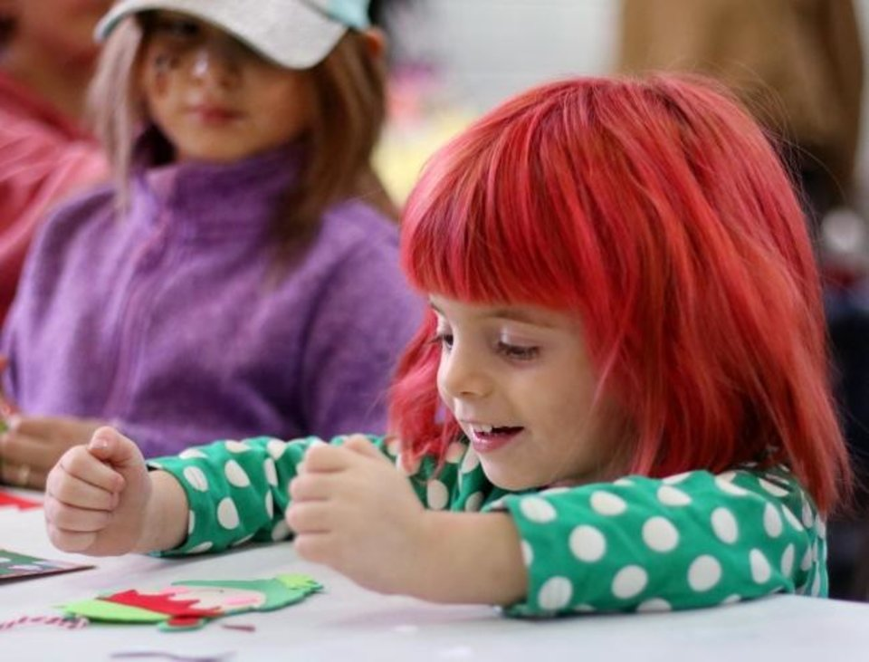 Photo -  Melanie McCracken, 3, and her sister, Delilah McCraken, 7 make ornaments at an ornament-making booth at the Oklahoma City Dream Center's