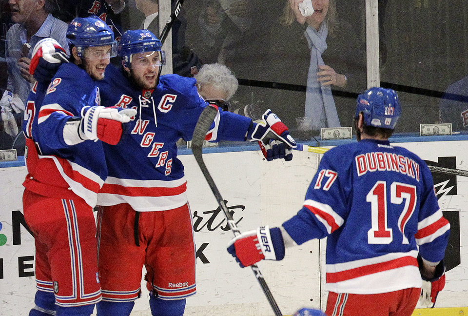 Photo -   New York Rangers' Ryan Callahan, center, is congratulated by Artem Anisimov, left, of Russia, and Brandon Dubinsky (17) after scoring a goal against the New Jersey Devils during the second period of Game 5 of an NHL hockey Stanley Cup Eastern Conference final playoff series, Wednesday, May 23, 2012, in New York. (AP Photo/Julio Cortez)