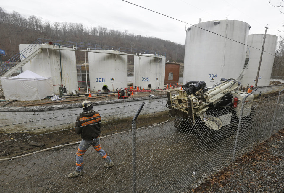 Photo - CORRECTS STATE TO W.VA. INSTEAD OF VA. - A worker moves a drilling machine   around storage tanks at Freedom Industries storage facility in Charleston, W.Va., Monday, Jan. 13, 2014. The ban on tap water for parts of West Virginia was lifted on Monday, ending a crisis for a fraction of the 300,000 people who were told not to drink, wash or cook with water after a chemical spill tainted the water supply. Gov. Earl Tomblin made the announcement at a news conference, five days after people were told to use the water only to flush their toilets. (AP Photo/Steve Helber)