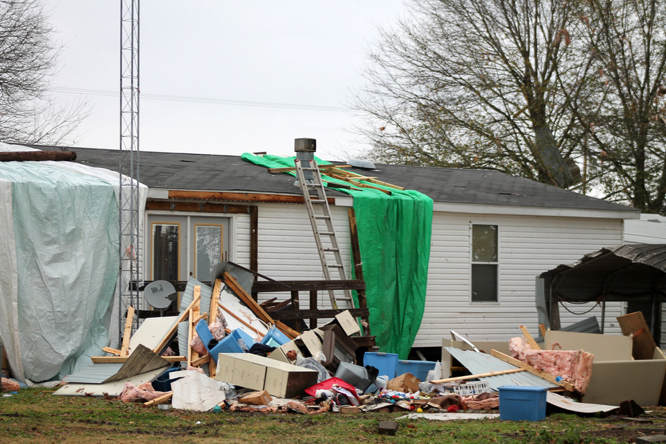 Photo - A tarp covers a tornado-damaged home in Halley, Ark., on Sunday, Dec. 22, 2013. A storm system swept across the central and southern U.S. on Saturday, bringing tornadoes to Arkansas and wind gusts that ripped roofs from barns and hurled trees into power lines, officials said.   (AP Photo/Andre P. Kissel)