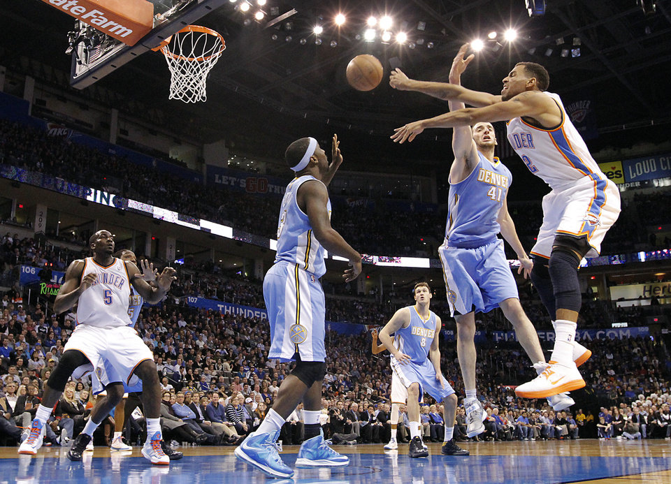 Photo - Oklahoma City's Thabo Sefolosha (2) passes the ball past Denver's Ty Lawson (3) and Kosta Koufos (41) during the NBA basketball game between the Oklahoma City Thunder and the Denver Nuggets at the Chesapeake Energy Arena on Wednesday, Jan. 16, 2013, in Oklahoma City, Okla.  Photo by Chris Landsberger, The Oklahoman