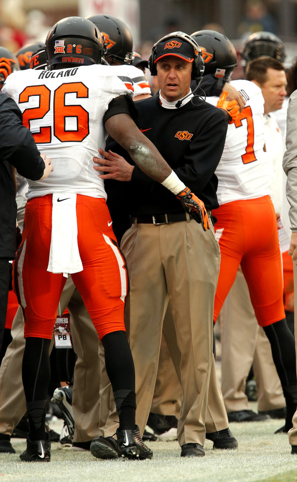 Photo - Cowboy head coach Mike Gundy congratulates Desmond Roland (26) after play during a Bedlam college football game between the University of Oklahoma Sooners (OU) and the Oklahoma State Cowboys (OSU) at Gaylord Family-Oklahoma Memorial Stadium in Norman, Okla., on Saturday, Dec. 6, 2014. Photo by Steve Sisney, The Oklahoman