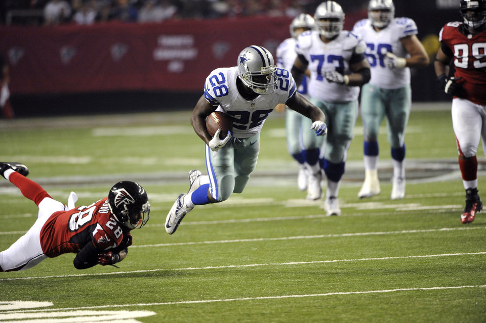Dallas Cowboys running back Felix Jones (28) gets by Atlanta Falcons safety Thomas DeCoud (28) during the second half of an NFL football game, Sunday, Nov. 4, 2012, in Atlanta. (AP Photo/David Tulis)