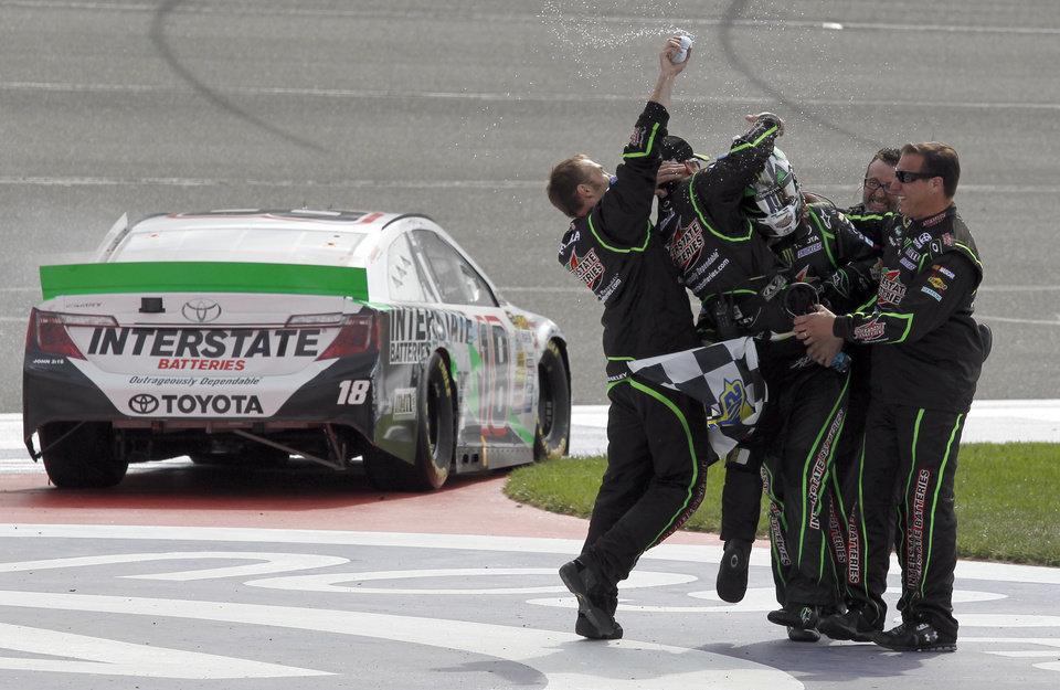 Photo - Kyle Busch, in helmet, celebrates with members of his team after winning the NASCAR Sprint Series auto race in Fontana, Calif., Sunday, March 23, 2014. (AP Photo/Alex Gallardo)
