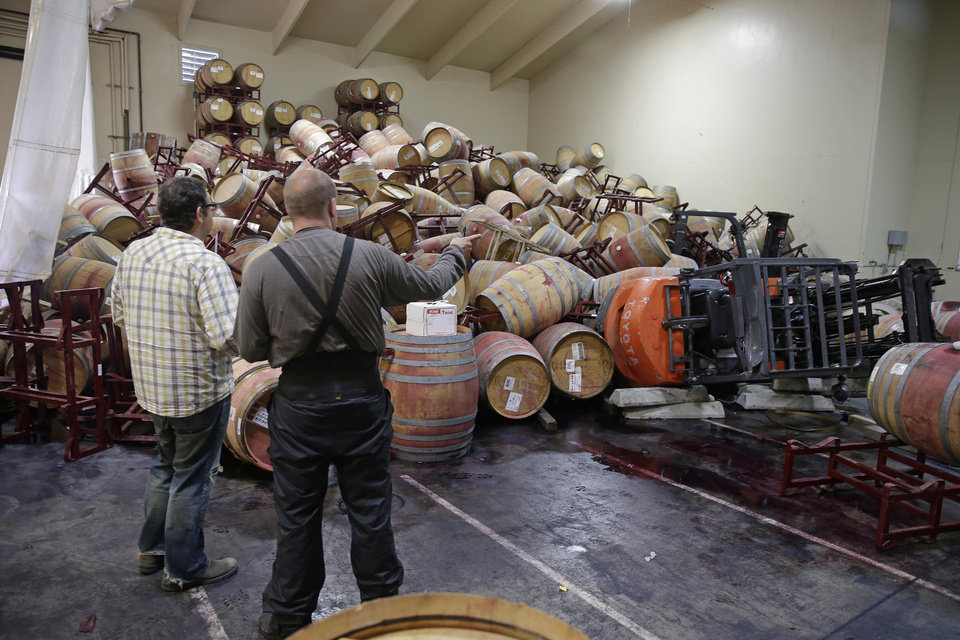Photo - Jeremy Weiss, left, and cellar worker Adam Craig, right, look over some of the hundreds of earthquake damaged wine barrels that covered and toppled a pair of forklifts at the Kieu Hoang Winery Monday, Aug. 25, 2014, in Napa, Calif. A powerful earthquake that struck the heart of California's wine country caught many people sound asleep, sending dressers, mirrors and pictures crashing down around them and toppling wine bottles in vineyards around the region. The magnitude-6.0 quake struck at 3:20 a.m. PDT Sunday near the city of Napa. (AP Photo/Eric Risberg)