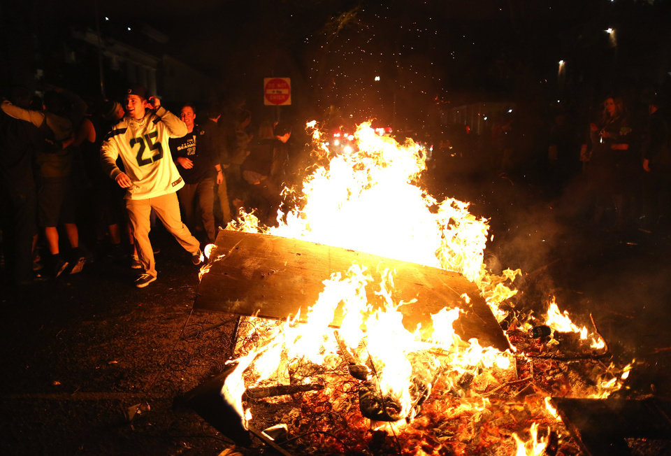 Students celebrate by setting a couch and other debris on fire at the University of Washington\'s Greek Row in Seattle after the Super Bowl Sunday, Feb. 2, 2014. The Seahawks, in their second Super Bowl appearance ever, won 43-8 over the Denver Broncos at MetLife Stadium in New Jersey. (AP Photo/The Seattle Times, Lindsey Wasson)