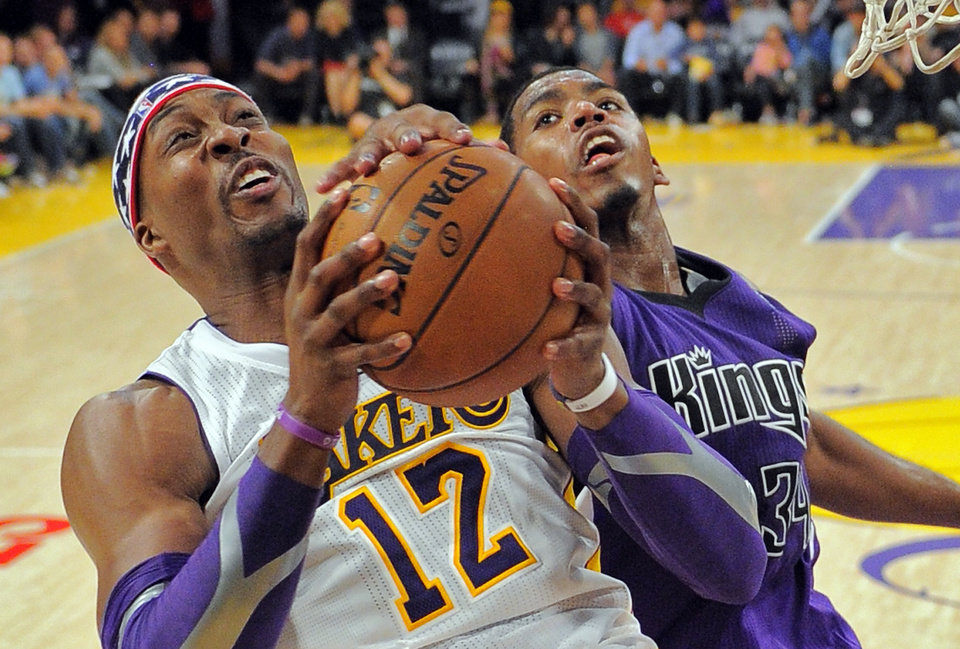 Los Angeles Lakers center Dwight Howard, left, puts up a shot as Sacramento Kings forward Jason Thompson defends during the second half of their NBA basketball game, Sunday, Nov. 11, 2012, in Los Angeles. The Lakers won 103-89. Howard had 23 points and 18 rebounds. (AP Photo/Mark J. Terrill)