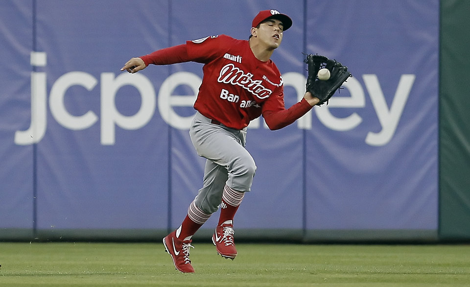 Mexico City Red Devils outfielder Leonardo Heras catches a fly ball for an out hit by Texas Rangers Ian Kinsler during the first inning of an exhibition baseball game Thursday, March 28, 2013, in Arlington, Texas. (AP Photo/Fort Worth Star-Telegram, Brandon Wade)