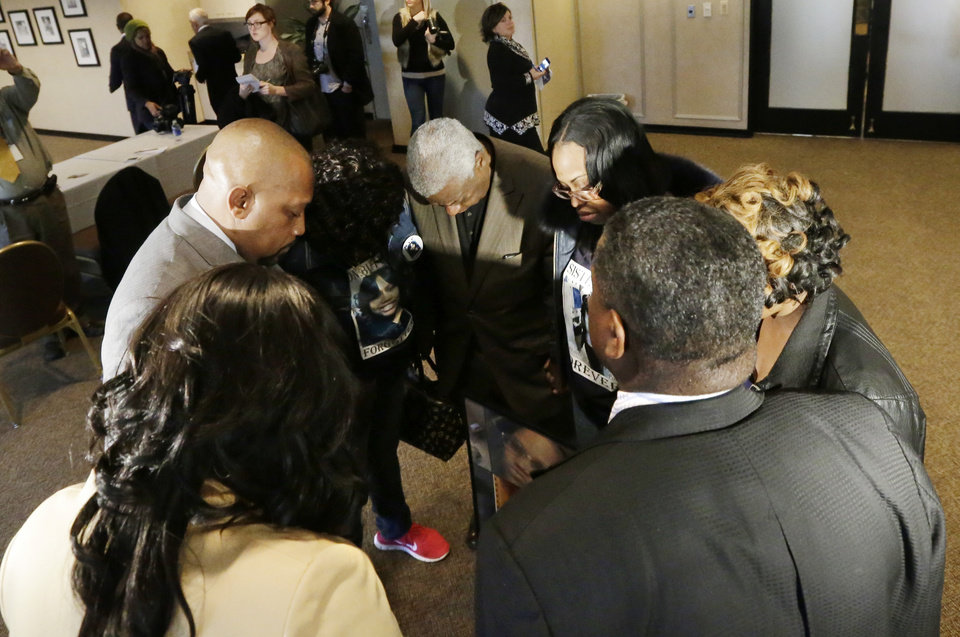 Photo - Family members and friends of Walter Ray Simmons and Monica McBride, the parents of Renisha McBride, pray at the conclusion of the news conference in Southfield, Mich., Friday, Nov. 15, 2013 where they responded to Wayne County Prosecutor Kym Worthy's decision announcement in the shooting death of their daughter Renisha McBride. Renisha was shot on Nov. 2  in the face on Theodore P. Wafer's front porch in Dearborn Heights. (AP Photo/Carlos Osorio)