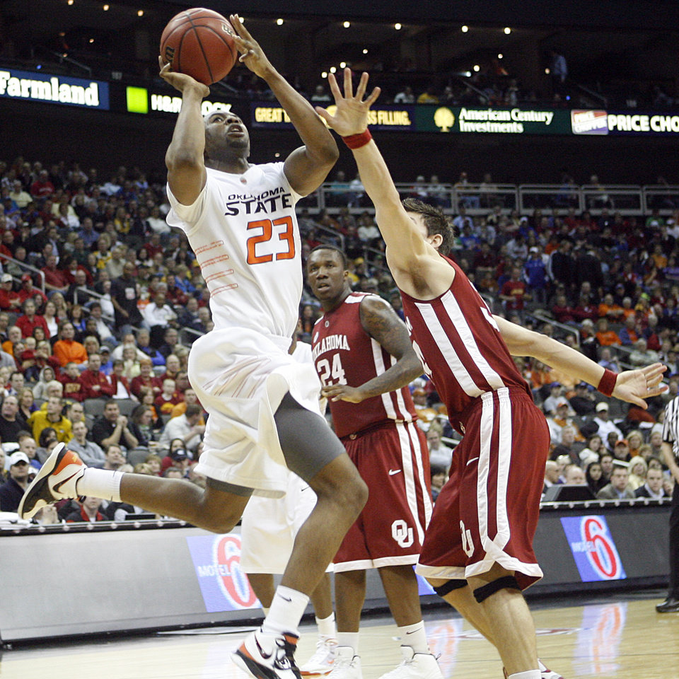 Photo - Oklahoma State's James Anderson (23) drives past Oklahoma's Cade Davis (34) in the second half of the college basketball game during the men's Big 12 Championship tournament at the Sprint Center on Wednesday, March 10, 2010, in Kansas City, Mo. Photo by Chris Landsberger, The Oklahoman