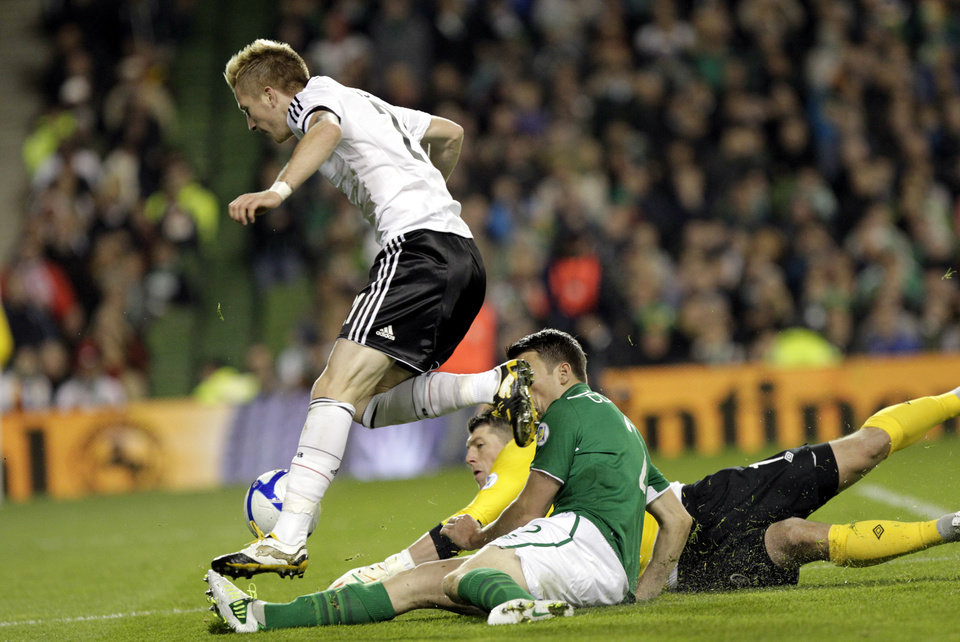 Photo -   Germany's Marco Reus, left, is challenged by Republic of Ireland's Seamus Coleman, right, and Keiren Westwood, center, during their World Cup Group C qualifying soccer match at the Aviva Stadium, Dublin, Ireland, Friday, Oct. 12, 2012. (AP Photo/Peter Morrison)