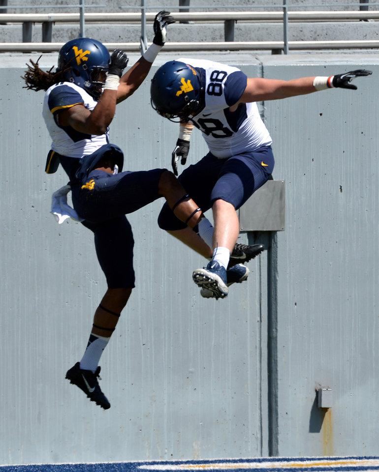Photo - West Virginia's Kevin White (11) celebrates his touchdown with Cody Clay (88) during their spring NCAA college football game in Morgantown, W.Va., Saturday, April 12, 2014. (AP Photo/Craig Cunningham)