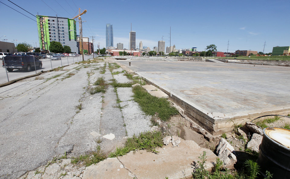 Photo - The Hilton Garden Inn can be seen rising in the background of what was once the Stewart Metal Fabricators complex in east Bricktown. Those slabs will be removed, and soil clean-up is set to begin next month as developers prepare to build housing, a hotel, retail and a garage.  PAUL B. SOUTHERLAND