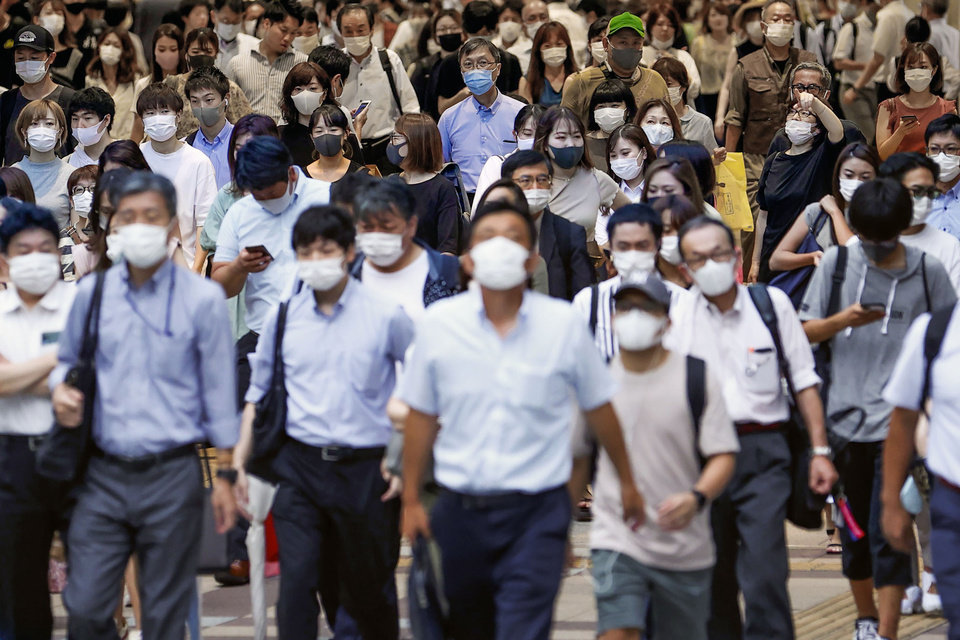 Photo -  People wearing face masks to help curb the spread of the new coronavirus walk across a street in Osaka, Japan, Wednesday, July 29, 2020. As Japan battles a surge in coronavirus cases, some areas may be running out of isolation facilities to monitor infected people.(Kyodo News via AP)