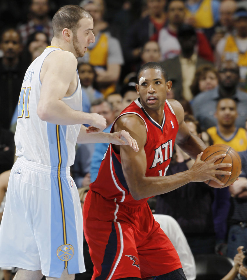 Atlanta Hawks forward Al Horford, right, pulls in a loose ball as Denver Nuggets center Kosta Koufos defends in the first quarter of an NBA basketball game in Denver on Monday, March 4, 2013. (AP Photo/David Zalubowski)