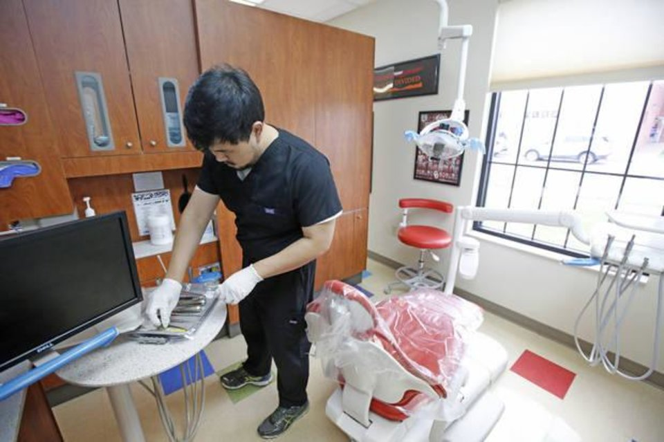 Photo -  Mason Kim, a volunteer dental assistant, places instruments on a tray Monday at the Good Shepherd clinic in Oklahoma City. The Good Shepherd clinic operates a weekly teeth extraction clinic on Monday evenings. [Photo By Steve Gooch, The Oklahoman]