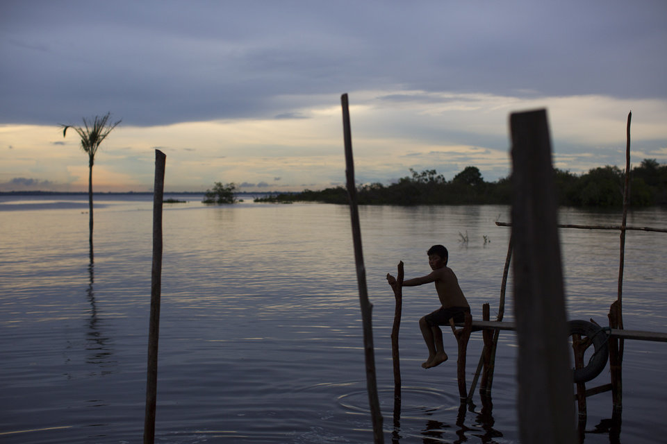 Photo - In this May 24, 2014 photo, a boy sits on a makeshift dock on the Rio Negro as the sun sets near Manaus, Brazil. Manaus, a World Cup host city, got its start as a Portuguese fort, founded in the late 17th century on the spot where the Rio Negro and the Solimoes River meet to form the immense Amazon, the planet's largest river by volume. (AP Photo/Felipe Dana)