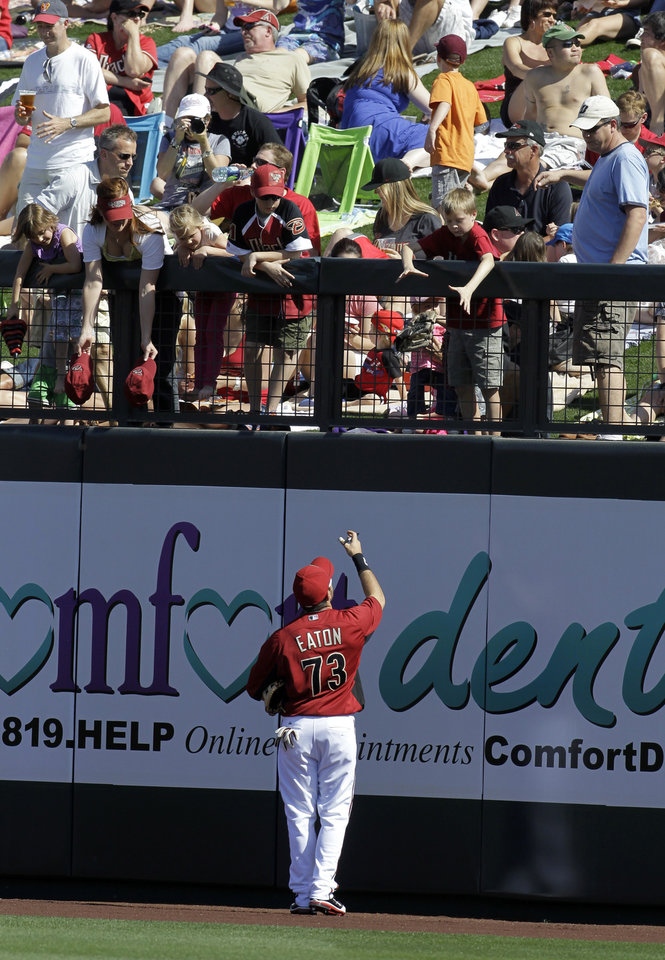 Photo -   Arizona Diamondbacks' Adam Eaton, bottom center, signs autographs for fans while the spring training baseball game against the San Francisco Giants is delayed, Sunday, March 4, 2012, in Scottsdale, Ariz. The game was delayed for 41 minutes because of a swarm of bees. (AP Photo/Darron Cummings)