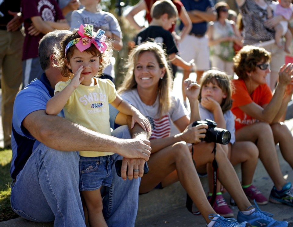 Photo - London Baldridge, 3, watches the Edmond Memorial High School homecoming parade with her father, Eric, and mother, Sunny, a teacher and coach for the school. PHOTO BY BRYAN TERRY, THE OKLAHOMAN.  Bryan Terry - THE OKLAHOMAN