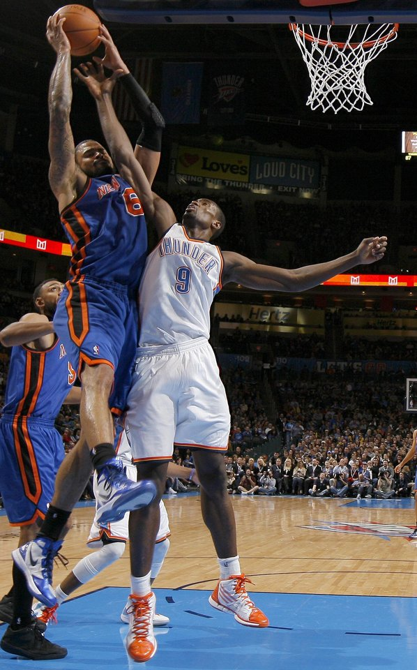 Photo - New York's Tyson Chandler (6) grabs a rebound over Oklahoma City's Serge Ibaka (9) during the NBA game between the Oklahoma City Thunder and the New York Knicks at Chesapeake Energy Arena in Oklahoma CIty, Saturday, Jan. 14, 2012. Photo by Bryan Terry, The Oklahoman