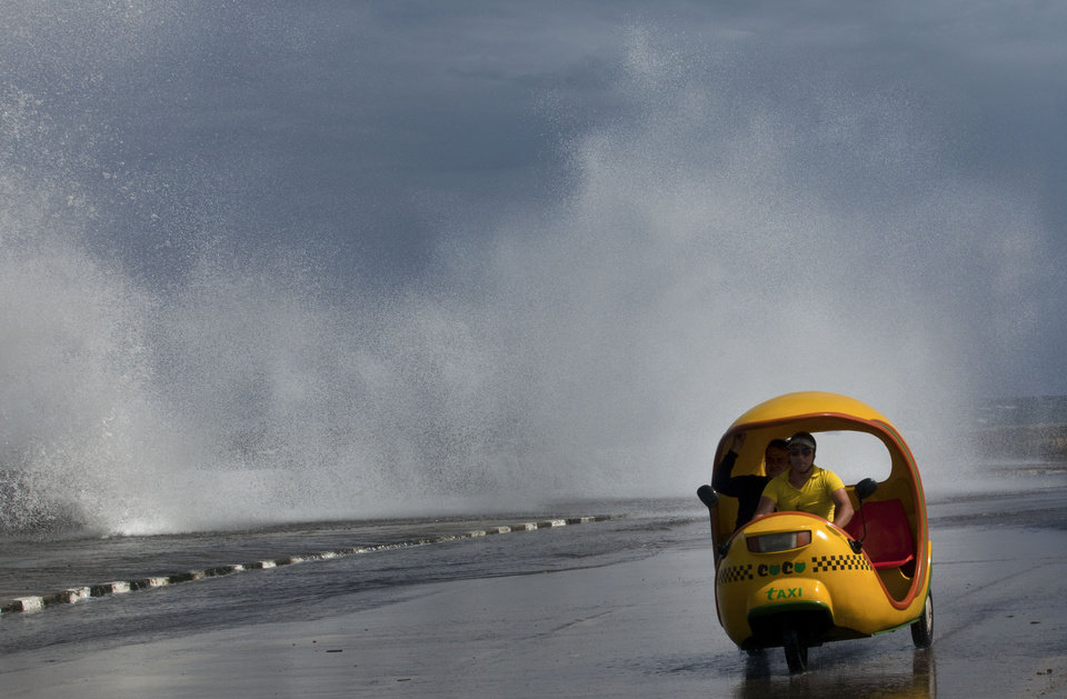 Photo -   A man drives his Coco-taxi as a wave crashes against the Malecon after the passing of Hurricane Sandy in Havana, Cuba, Thursday, Oct. 25, 2012. Hurricane Sandy blasted across eastern Cuba on Thursday as a potent Category 2 storm and headed for the Bahamas after causing at least two deaths in the Caribbean. (AP Photo/Ramon Espinosa)