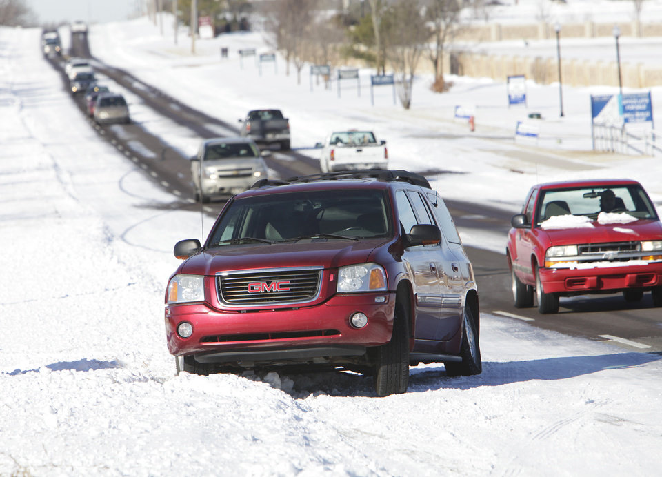 Photo - An SUV rests on the curb in a pile of snow on 33rd just west of Santa Fe, Thursday, February 10 , 2011. Photo by David McDaniel, The Oklahoman