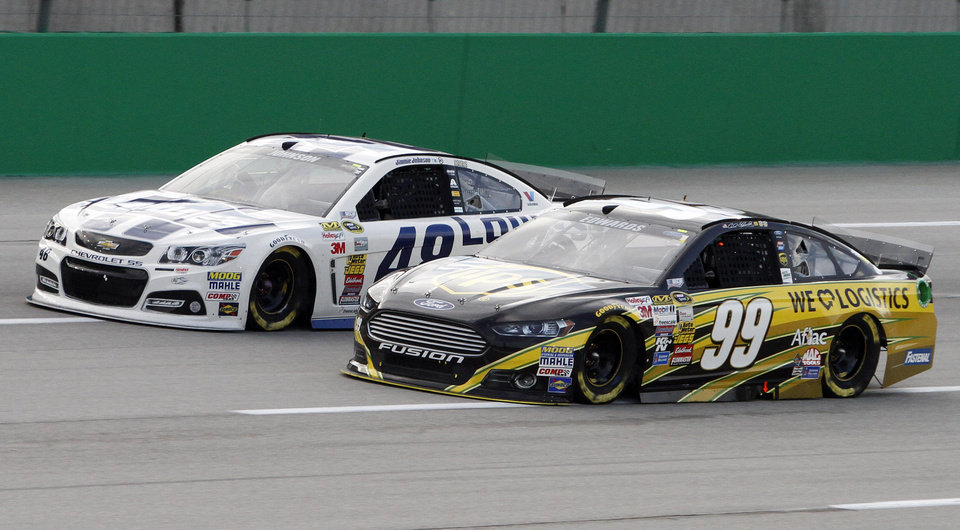 Photo - Jimmie Johnson (48) and Carl Edwards (99) drive during the NASCAR Sprint Cup series auto race Saturday, June  28, 2014 at Kentucky Speedway in Sparta, Ky. (AP Photo/James Crisp)