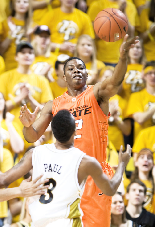 Photo - Oklahoma State's Obi Muonelo, top, pulls down a rebound over Missouri's Miguel Paul, bottom, on Saturday. AP photo