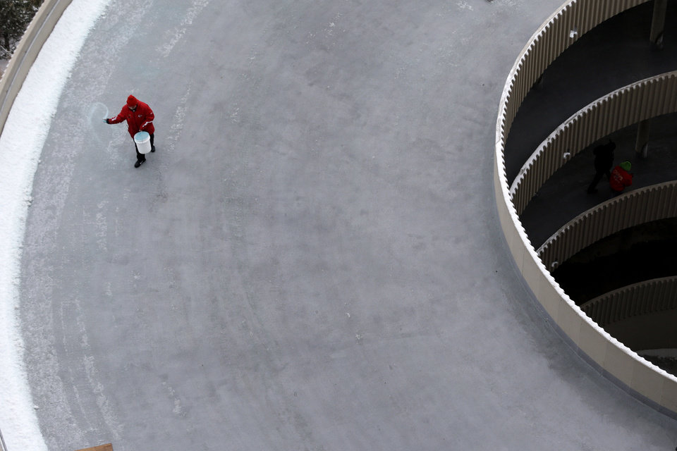 Photo - A worker applies ice melt to to a ramp at Arrowhead Stadium before an NFL football game between the Kansas City Chiefs and the Indianapolis Colts Sunday, Dec. 22, 2013, in Kansas City, Mo. (AP Photo/Charlie Riedel)