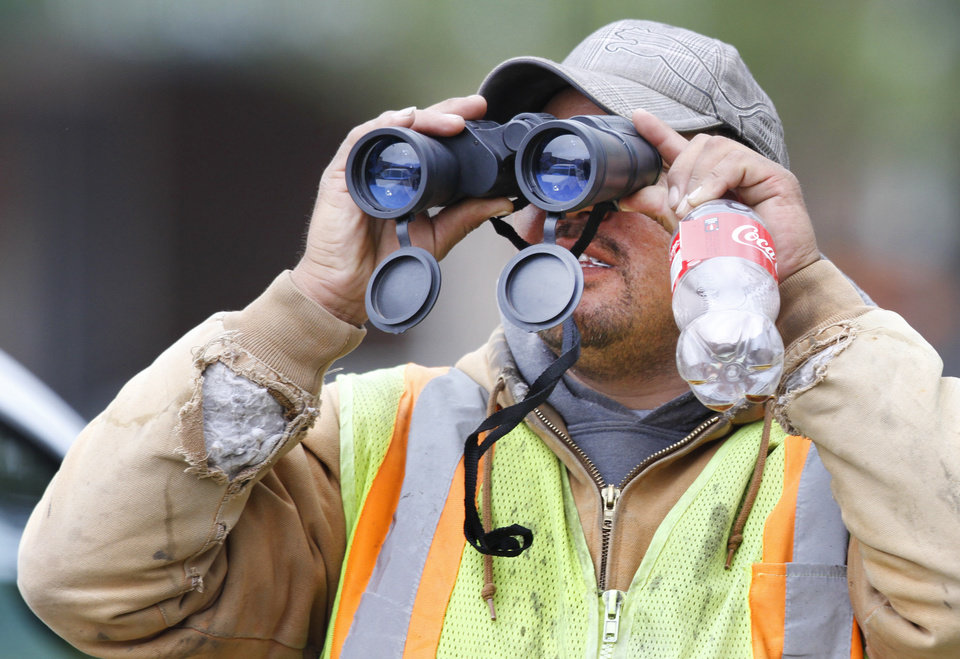 Photo - BOMB SCARE: Construction worker Lolo Markes uses binoculars to watch members of the Oklahoma City Police Bomb Squad search a U-Haul truck parked on Walker Avenue in downtown Oklahoma City , Wednesday April 17, 2013. Photo By Steve Gooch, The Oklahoman ORG XMIT: OKC1303121532440650