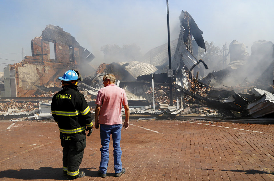 Photo -  Seminole firefighter Nick Pepe talks with Terry Gray, the town's code enforcement officer, Monday as they view what remains of downtown buildings after a weekend fire. Pepe was among dozens of firefighters who battled the blaze most of Sunday. [Photo by Jim Beckel, The Oklahoman]