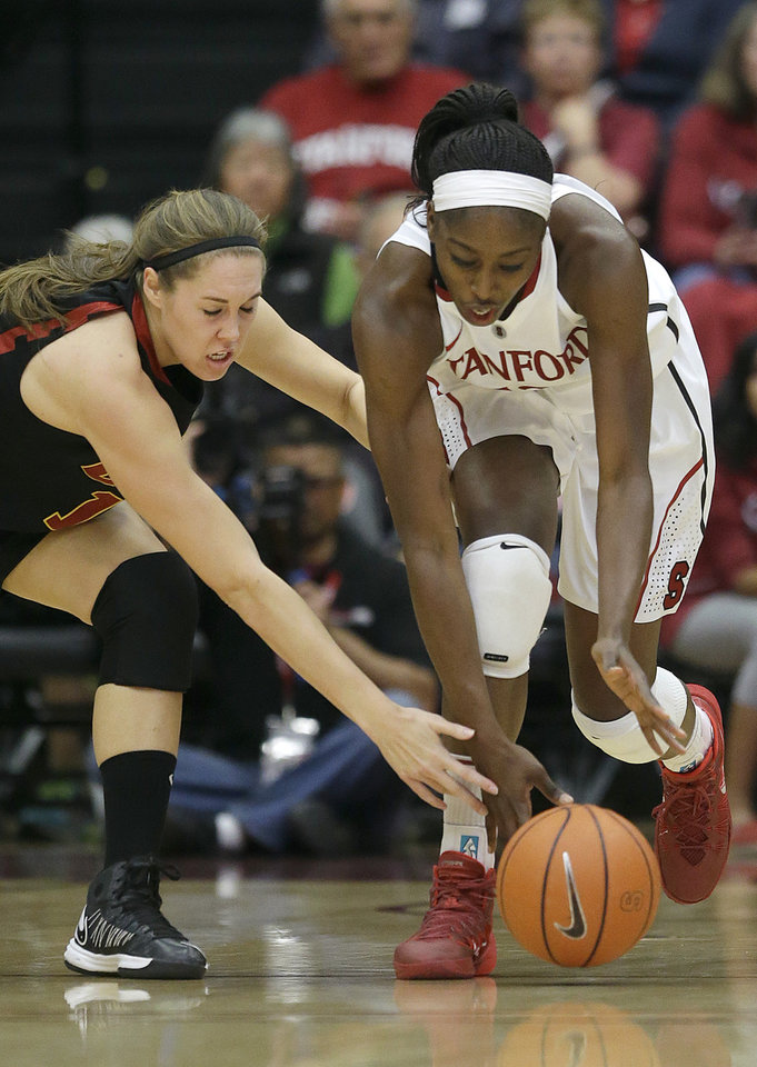 Photo - Stanford forward Chiney Ogwumike, right, reaches for a loose ball in front of USC forward Cassie Harberts during the first half of an NCAA college basketball game in Stanford, Calif., Monday, Jan. 27, 2014. (AP Photo/Jeff Chiu)