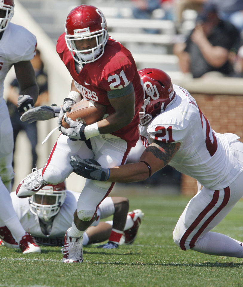 Photo - Running back Brennan Clay (21) is tackled by line backer Tom Wort (21) during the University of Oklahoma Sooner's (OU) Spring Football game at Gaylord Family-Oklahoma Memorial Stadium on Saturday, April 16, 2011, in Norman, Okla.  