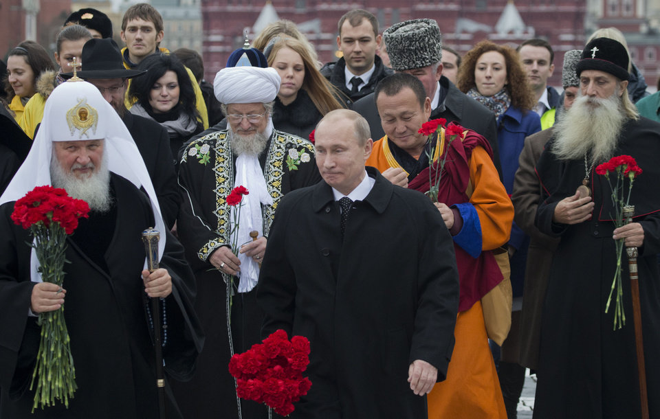 Photo -   Russian President Vladimir Putin, center, walks alongside religious leaders of various denominations at the Red Square as they go to place flowers at a statue of Minin and Pozharsky, the leaders of a struggle against foreign invaders in 1612, to mark the National Unity Day, Sunday, Nov. 4, 2012. The new holiday was created in 2005 to replace the traditional Nov. 7 celebration of the 1917 Bolshevik rise to power. The Kremlin has tried to give it historical significance by tying it to the 1612 expulsion of Polish and Cossack troops who briefly seized Moscow at a time of political disarray. (AP Photo/ Misha Japaridze)